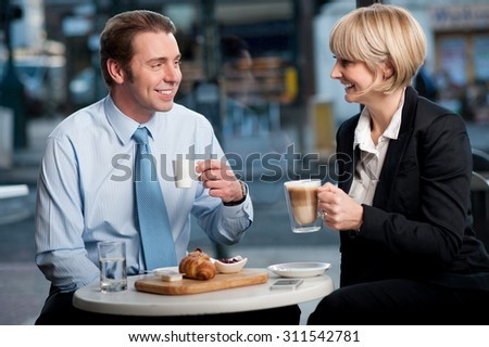 Happy business partners having coffee at cafe - stock photo