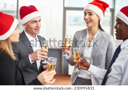Happy business partners in Santa caps holding flutes with champagne at corporate party - stock photo