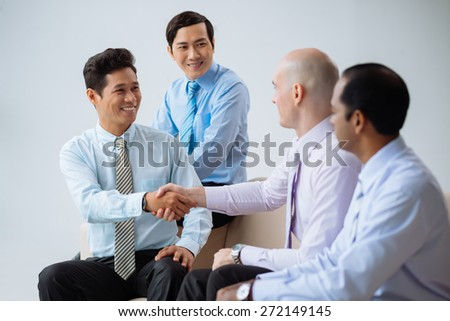 Happy business partners shaking hands after successful deal - stock photo