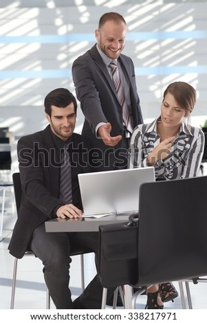 Happy business partners sitting at coffee table in office lobby talking over laptop, working together. - stock photo
