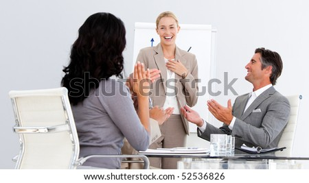 Happy business people applauding a good presentation in the office - stock photo