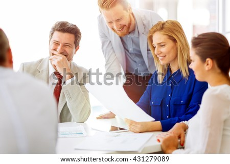Happy business people brainstorming in office - stock photo