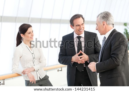 Happy business people discussing in the hallway - stock photo