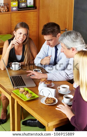 Happy business people having a meeting with laptop in a caf�© - stock photo