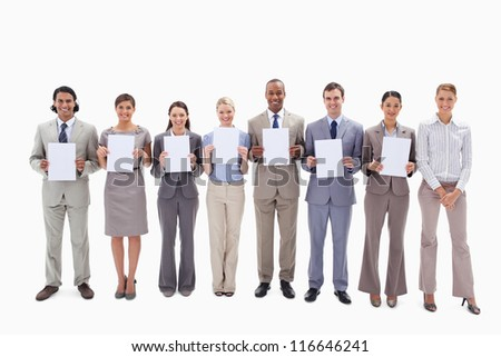 Happy business people holding seven white supports for letters against white background - stock photo