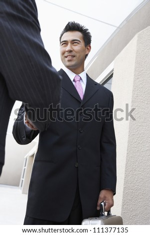 Happy business people in suit shaking hands