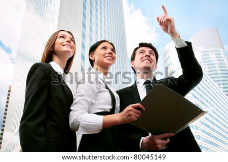 Happy business people on the background of a modern office building - stock photo