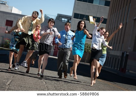 Happy business people running in the street - stock photo