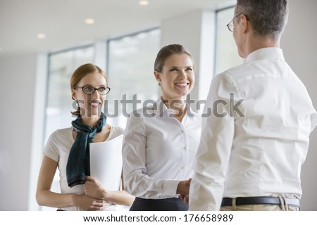 Happy business people shaking hands in office - stock photo