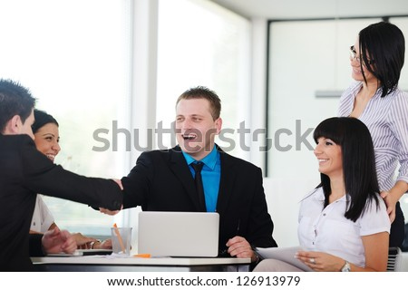 Happy business people shaking hands on a deal and smiling over working table - stock photo
