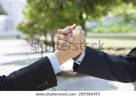 Happy business people shaking hands outside  - stock photo