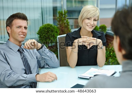 Happy business people sitting around table outdoor on office terrace and talking, smiling. Over the shoulder view. - stock photo