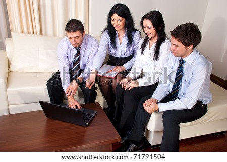 Happy business people sitting on a couch and having  a conversation together about what they see on a laptop - stock photo