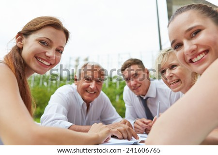 Happy business people sitting together during meeting outdoors on a table