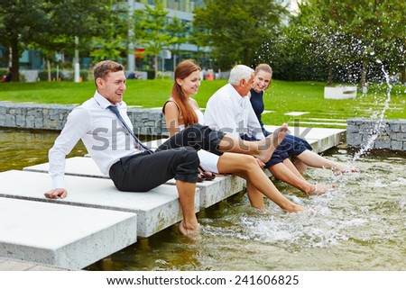 Happy business people splashing water in summer with their feet - stock photo