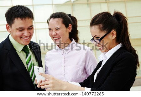 Happy business people standing and looking at mobile phone - stock photo