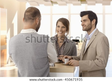 Happy business people standing at coffee table at office, talking.