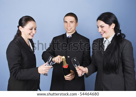 Happy business people team celebrating with champagne and having fun together on blue background - stock photo
