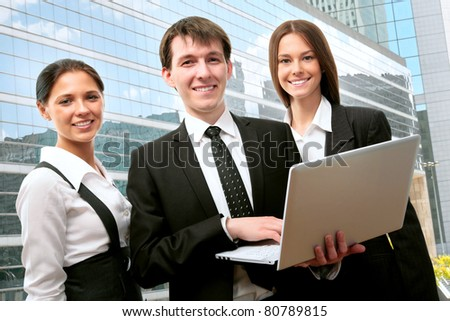 Happy business people using laptop on background of a modern office building