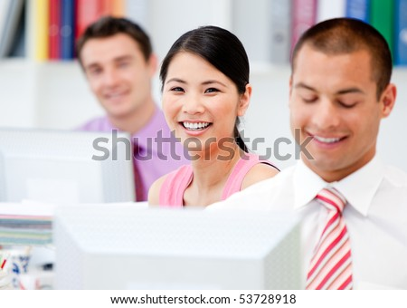 Happy business people working at a computer in the office - stock photo