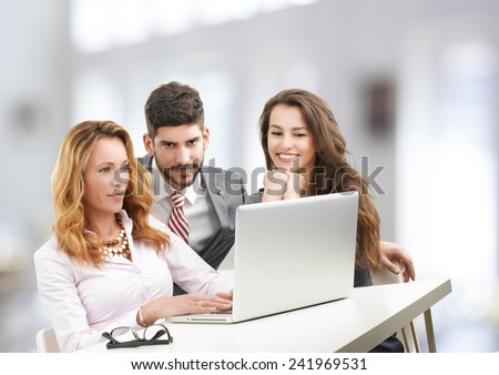 Happy business team analyzing financial data on laptop while sitting at office.  - stock photo