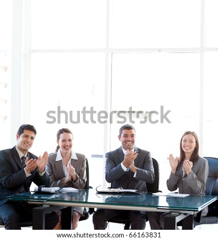Happy business team applauding during a presentation sitting around a table