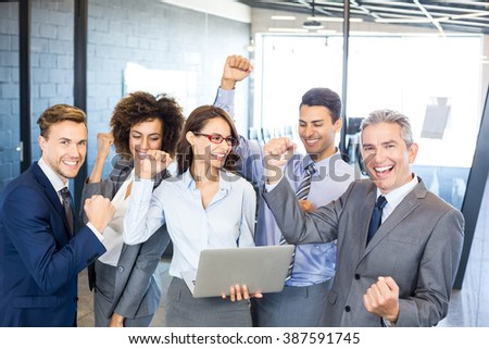 Happy business team celebrating a success in office - stock photo