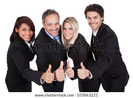 Happy business team celebrating a success with thumbs up on white background