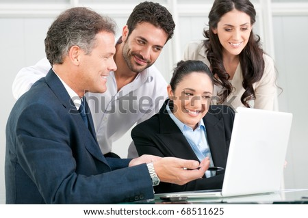 Happy business team discussing and working together at office meeting with laptop - stock photo