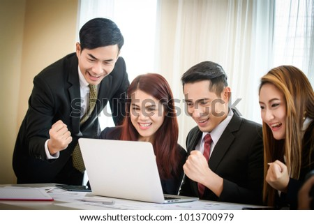 Happy business team enjoy good news together from email on laptop.