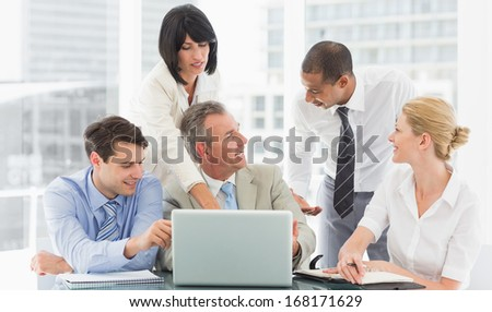 Happy business team gathered around laptop talking in the office