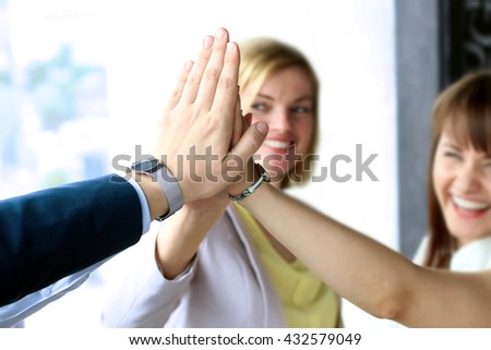 happy business team giving high five in office - stock photo