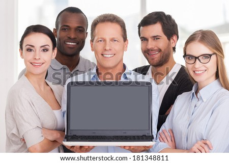 Happy business team. Group of cheerful business people in casual wear standing close to each other while mature man showing laptop monitor and smiling - stock photo