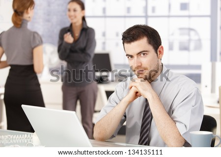 Happy business team having break in office, women chatting in background, man sitting at desk. - stock photo