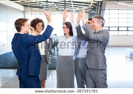 Happy business team high fiving in office - stock photo