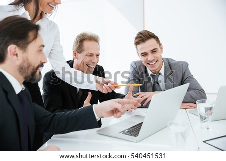 Happy Business team looking at laptop by the table in office