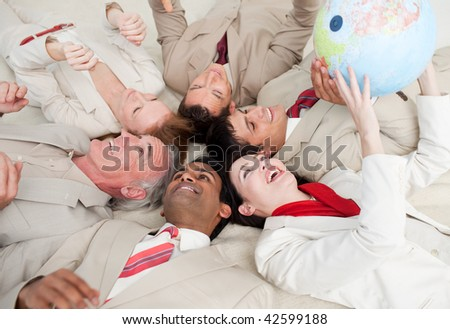 Happy business team lying on the floor playing with a terrestrial globe - stock photo