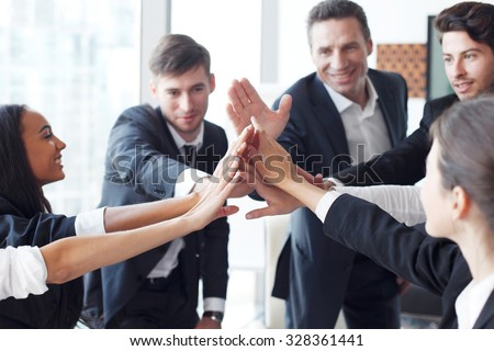 Happy business team making high five with their hands in the office - stock photo