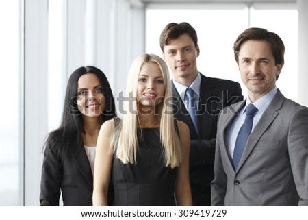 Happy business team of coworkers in office - stock photo