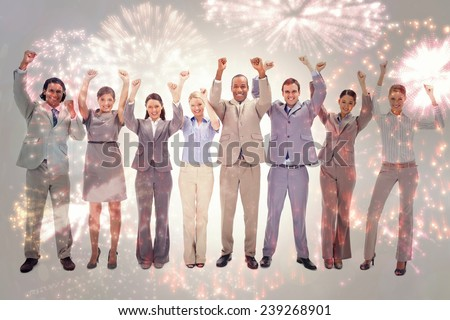 Happy business team raising their arms against colourful fireworks exploding on black background - stock photo