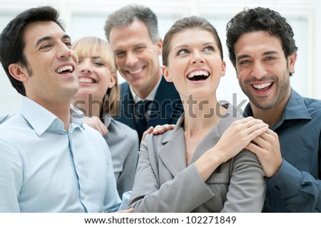 Happy business team smiling and laughing together at office to celebrate a success - stock photo