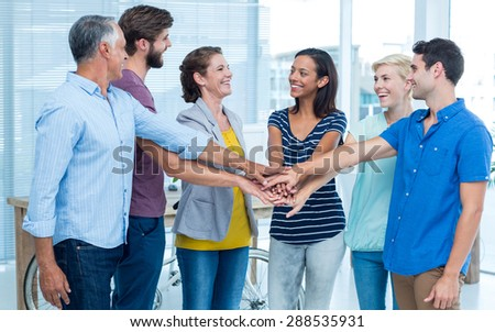 Happy business team stacking their hands together - stock photo