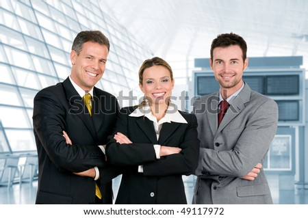 Happy business team standing with crossed arms in their modern office - stock photo