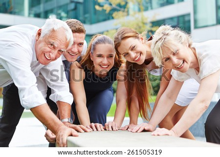 Happy business team working and pushing together for success outdoors - stock photo