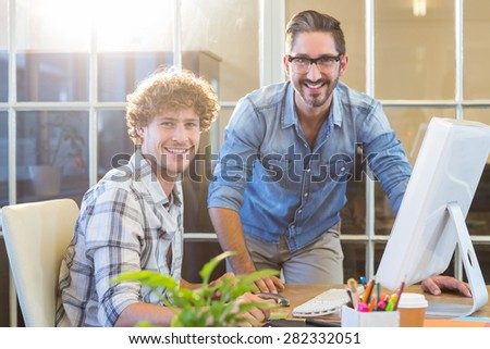 Happy business team working on computer in the office - stock photo