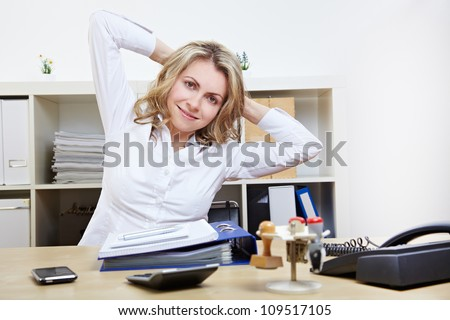 Happy business woman doing back exercises at work in her office - stock photo