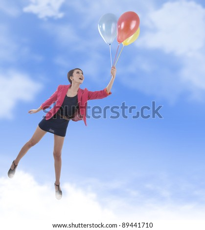 Happy business woman flying with colorful balloon - stock photo