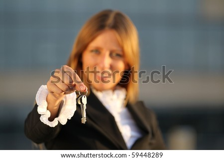 Happy Business woman hand holding key. Focus on keys - stock photo
