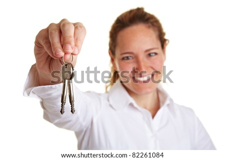 Happy business woman holding two keys in her hand - stock photo