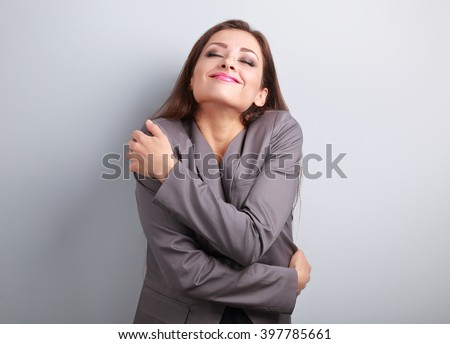 Happy business woman hugging herself with natural emotional enjoying face. Love concept of yourself - stock photo